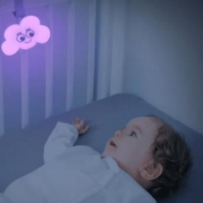 luz de la noche de la nube que cuelga de las barras de la cuna. niño acostado en la cama y mirando la luz de la noche de la nube